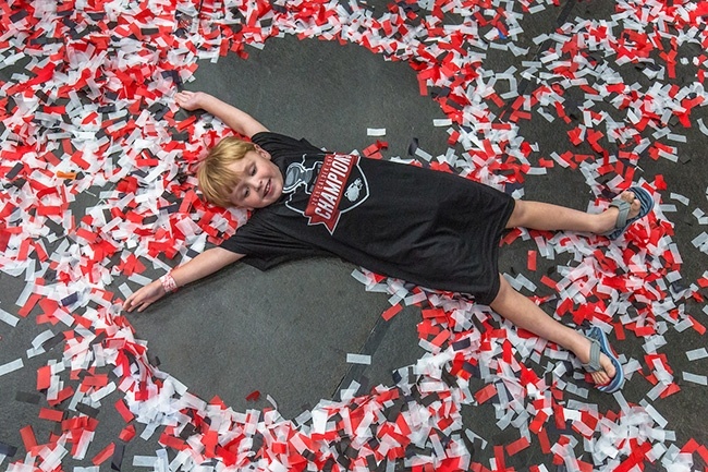 "A young Charlotte Checkers fan makes a ""confetti angel"" as the team celebrates their Calder Cup Championship win."