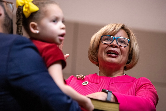 Charlotte Mayor Vi Lyles is sworn in for her second term with her hand on a bible held by her granddaughter.