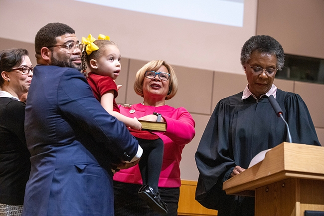 Charlotte Mayor Vy Lyles is sworn in for her second term with her hand on a bible held by her daughter.
