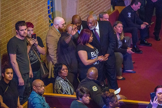 Dr. Jones, Pastor of Friendship Missionary Baptist Church (right), after calling for mutual respect when some community members began to yell, stood with those individuals to talk with them further.