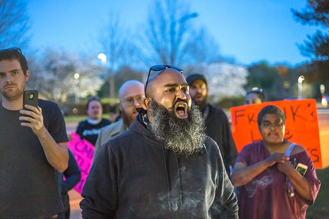 Andrew Woods (center) and other protesters chant outside of Friendship Missionary Baptist Church in response to the community meeting held by CMPD inside.