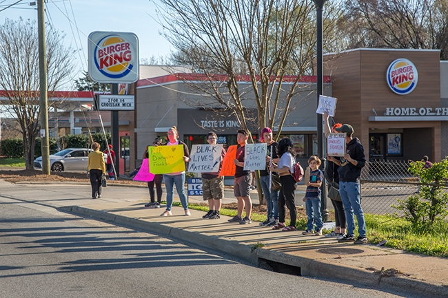 Individuals gather in front of a Burger King on Beatties Ford Road at a planned rally to honor Danquirs Franklin, who was shot and killed during an altercation with police earlier in the week.