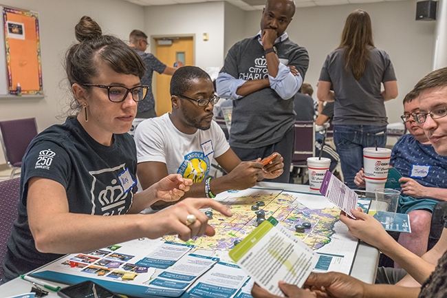 "Charlotte City Planning Director Taiwo Jaiyeoba  (standing) listens as partipcants play the ""Growing Better Places: A More Equitable and Inclusive Charlotte"" board game."