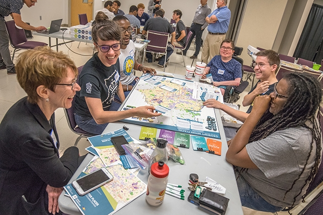 """Garet Johnson, Assistant Director of Planning/Project Manager of Charlotte Future 2040 Comprehensive Plan (bottom left) talks with participants as they play the """"Growing Better Places: A More Equitable and Inclusive Charlotte"""" board game."""