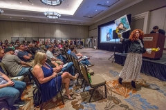 Volunteers at the Heroes Convention 2019 art auction, Westin Hotel, walk items up for auction around for attendees to see more closely before the bid.