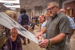 Heroes Convention founder Shelton Drum inspects one of many items of art up for sale at Saturday's auction.