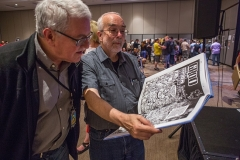 Heroes Convention 2019 attendees inspect one of many items of art up for sale at Saturday's auction.