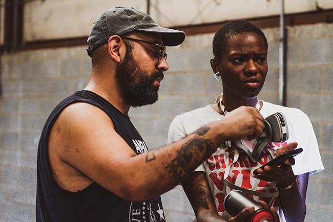 Alex DeLarge talks to Dari Calamari during a META spray-painting class.