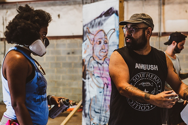 Lo'Vonia Parks listens to Alex DeLarge during a META spray-painting class.