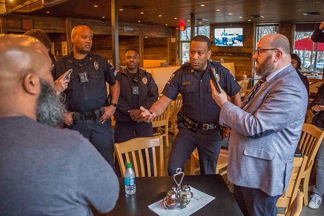 CMPD officers listen and talk with Andrew Woods and supporting protesters who made demands about changes they want made in how the company deals with black and LGBTQ employees during a brief sit-in at the Plaza Midoowd Pizza Peel location.