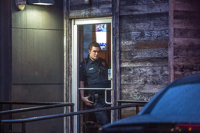 A CMPD officer stands at the door of the Plaza Midwood Pizza Peel location during a brief sit-in.